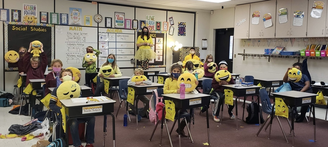 class wearing yellow with emoji pillows