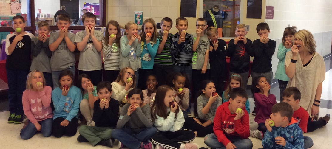 students posing with apples on apple crunch day